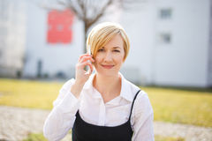 Blonde woman in formal wear calling outdoor Royalty Free Stock Photography