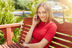 Blonde woman with freckles having gentle smile while sitting at wooden comfortable bench in park and communicating with her best f. Riend over mobile phone Stock Photo