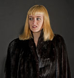 Blonde woman in fur coat Stock Photos