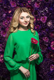 Blonde woman with a gentle make-up that looks at the camera while holding flower near the face on a floral background. Portrait of a beautiful blonde woman with Royalty Free Stock Image