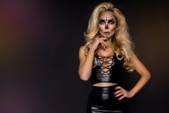 Blonde woman in Halloween makeup and leather outfit on a black background in the studio. Skeleton, monster and witch. Blonde woman girl in Halloween makeup and stock photo