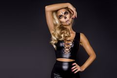Blonde woman in Halloween makeup and leather outfit on a black background in the studio. Skeleton, monster and witch. Blonde woman girl in Halloween makeup and stock images