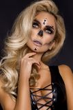 Blonde woman in Halloween makeup and leather outfit on a black background in the studio. Skeleton, monster and witch. Blonde woman girl in Halloween makeup and stock image