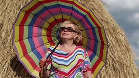 Blonde woman in glasses with many-coloured umbrella stays near haystack stock footage