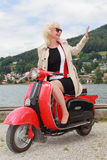 Blonde woman goes waving with the scooter on the lake Stock Photo