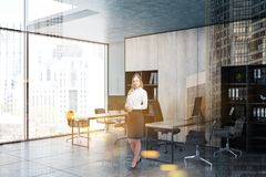 Blonde woman in gray and wooden office corner royalty free stock image