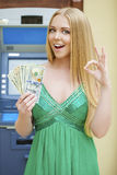 Blonde woman in a green dress is holding a cash dollars Royalty Free Stock Image