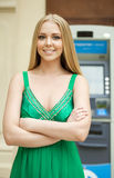 Blonde woman in a green dress looks at the background of the ATM Royalty Free Stock Images