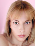 Blonde woman with green eyes. Close-up of a blonde woman on pink background Royalty Free Stock Photo