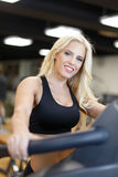 Blonde woman in gym on treadmill Stock Photography