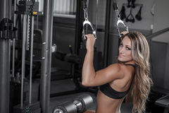 Blonde woman in gym workout. Pulldown exercise Stock Image