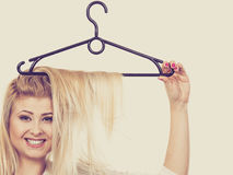 Blonde woman with hair in clothes hanger royalty free stock photography