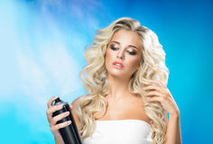 Blonde woman with a hair spray Royalty Free Stock Photos