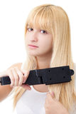Blonde Woman with Hair Straightener Stock Images