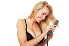 Blonde woman with hair straightener Royalty Free Stock Images