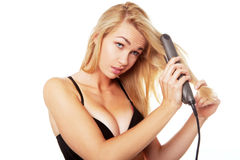 Blonde woman with hair straightener Stock Photo