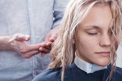A blonde woman in hair studio. A hairdresser making a haircut for a blonde female client Stock Photo