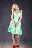 Blonde woman with hair in the wind. sexy girl with flying hair posing in green dress and red shoes Stock Photos