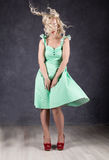 Blonde woman with hair in the wind. sexy girl with flying hair posing in green dress and red shoes.  Royalty Free Stock Photo