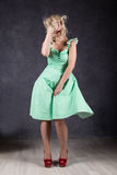 Blonde woman with hair in the wind. sexy girl with flying hair posing in green dress and red shoes.  Stock Photo