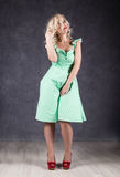 Blonde woman with hair in the wind. sexy girl with flying hair posing in green dress and red shoes.  Stock Image