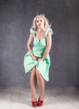 Blonde woman with hair in the wind. sexy girl with flying hair posing in green dress and red shoes.  Royalty Free Stock Image