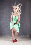 Blonde woman with hair in the wind. sexy girl with flying hair posing in green dress and red shoes.  Stock Photos