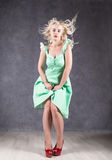Blonde woman with hair in the wind. sexy girl with flying hair posing in green dress and red shoes.  Royalty Free Stock Images
