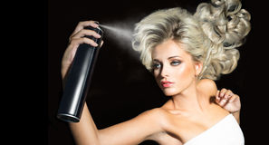 Blonde woman with a hairspray Royalty Free Stock Photography