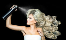 Blonde woman with a hairspray Stock Images