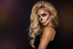 Blonde woman in Halloween makeup and leather outfit on a black background in the studio. Skeleton, monster and witch. Blonde woman girl in Halloween makeup and stock photography