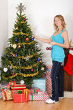 Blonde woman hanging christmas ornament on tree Royalty Free Stock Images