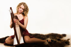 Blonde woman with a harp in his hand Royalty Free Stock Photos