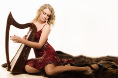 Blonde woman with a harp in his hand Royalty Free Stock Photography