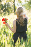 Blonde woman harvesting flowers Royalty Free Stock Photos