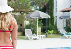 Blonde woman in a hat relaxing by a swimming pool Royalty Free Stock Image
