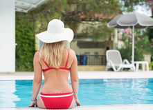 Blonde woman in a hat relaxing by a swimming pool Royalty Free Stock Images