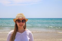 Blonde woman with hat and sunglasses on the sea royalty free stock photo