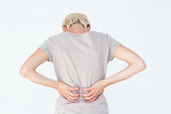 Blonde woman having a back ache and holding her back Royalty Free Stock Photography
