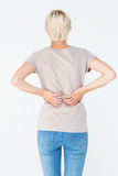 Blonde woman having a back ache and holding her back Stock Images