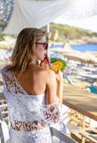 Blonde woman is having a cocktail at a beach bar during summer time stock photos