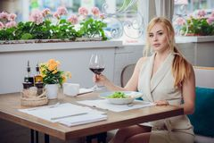 Blonde woman having lunch at the restautant stock images