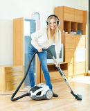 Blonde woman in headphones cleaning with vacuum cleaner Stock Photography