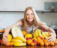 Blonde   woman with heap of fruits Royalty Free Stock Images