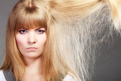 Blonde woman with her damaged dry hair. Royalty Free Stock Image