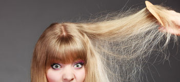 Blonde woman with her damaged dry hair. Royalty Free Stock Photography