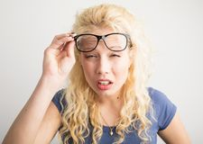 Woman with her glasses lifted up can`t see. Blonde woman with her glasses lifted up can`t see Royalty Free Stock Image