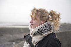 Blonde woman in her twenties at the beach. On a winters day Stock Image