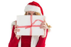 Blonde woman hiding behind a gift. On white background Royalty Free Stock Image