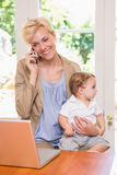 Blonde woman with his son using phone and laptop. Blonde women with his son using phone and laptop in the office Stock Photography